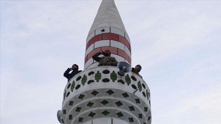 Köylüler telefon görüşmesi yapabilmek için minare önünde sıraya giriyor